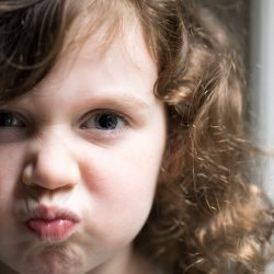 Macro close up portrait of a young child girl kids face angry pursed lips curly brown hair lit by